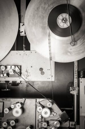 35 mm: Rare industrial cinema 35 mm movie printer detail vintage black and white, analog optical process with rgb lamps and reels in post production factory