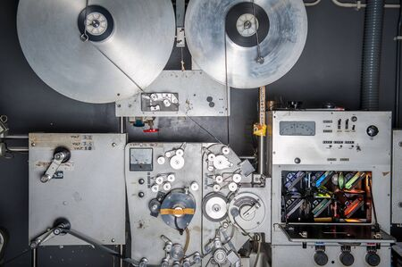 35 mm: Rare vintage industrial cinema 35 mm movie printer with film loaded, analog optical process with rgb lamps in post production factory