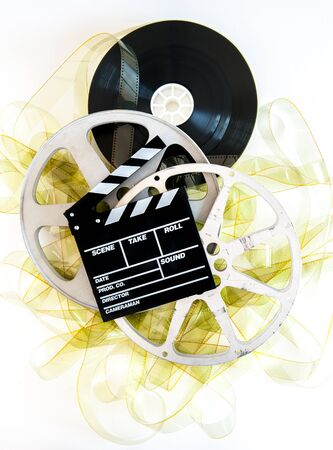 35mm: Movie clapper on 35mm yellow unrolled film and cinema reels on neutral background vertical frame