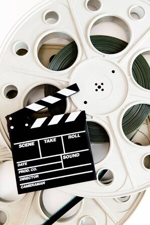 35 mm: Movie clapper on two 35 mm cinema reels with film vertical frame on white background Stock Photo