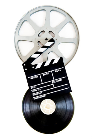 35mm: Movie clapper on two 35mm film reels isolated on white background vertical