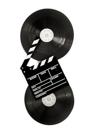 35 mm: Movie clapper on 35 mm cinema film reels isolated on white background vertical frame