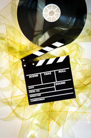 35 mm: Movie clapper on 35 mm cinema reel unrolled yellow filmstrip on white background vertical Stock Photo