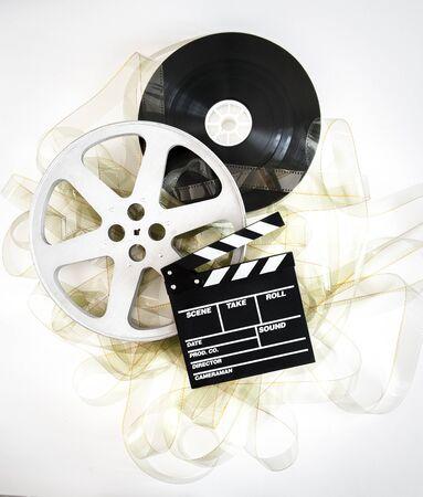 35 mm: Movie clapper on 35 mm cinema reels unrolled filmstrip on neutral background