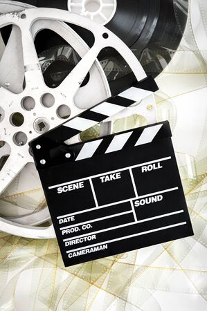 Movie clapper on 35 mm cinema reels unrolled filmstrip on white background vertical photo