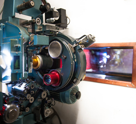 35 mm: 35 mm movie cinema projector machine in projectionist room with out of focus cinema screen in theater