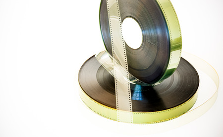 35 mm: Two 35 mm movie film reels, one vertical other one horizontal,   vintage color effect on white background Stock Photo