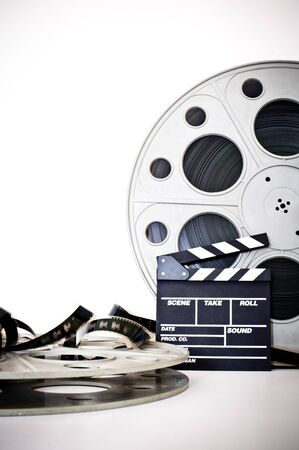 35 mm: Movie clapper and vintage 35 mm film cinema reel on white background filmstrip unrolled Stock Photo