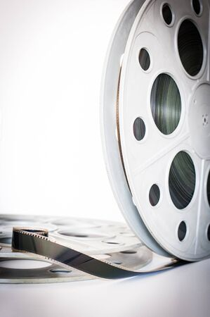 35 mm: Vintage 35 mm movie cinema reel on white background film unrolled and copy space vertical frame
