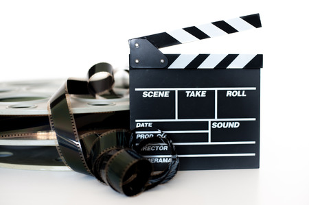 35 mm: Movie clapper and vintage 35 mm film cinema reel on white background filmstrip unrolled selective focus Stock Photo