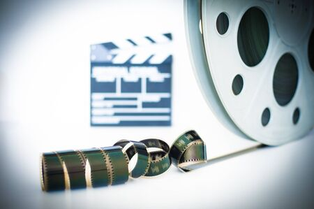 35 mm: Movie clapper and 35 mm film roll on white background and selective focus