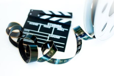 35 mm: Movie clapper and vintage 35 mm film cinema reel on white background filmstrip selective focus