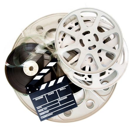 35mm: Movie clapper board and different cinema 35mm film reel isolated on white background