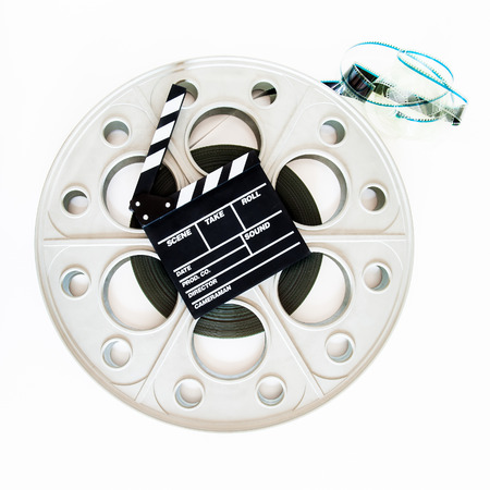 35mm: Movie clapper board on  vintage big 35mm film big reel for cinema projector on white background Stock Photo