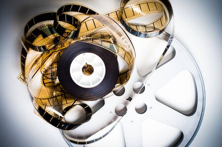 35 mm: Unrolled 35 mm film on movie reel on white background vintage color effect Stock Photo
