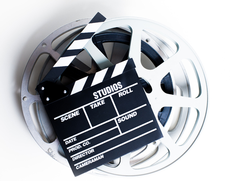 Movie clapper with vintage empty film reels on white background