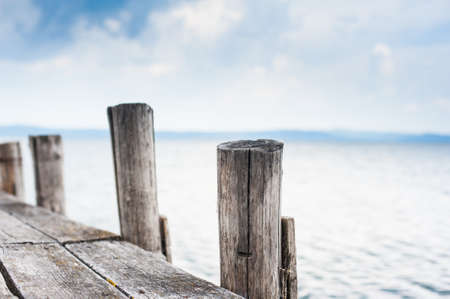 stake: Wooden jetty stake in autumn day with out of focus lake in background Stock Photo