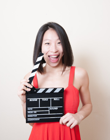 sneer: Funny pretty asian woman with red dress and movie clapperboard on white background