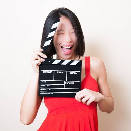 smirk: Funny pretty asian woman with red dress and movie clapperboard on white background