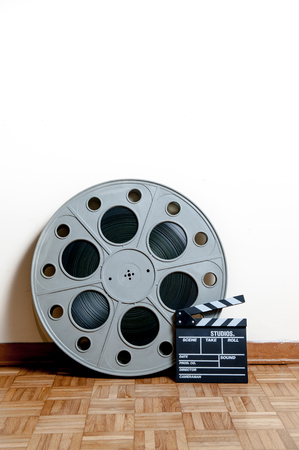 35 mm: 35 mm cinema movie roll with clapper on wooden floor and white wall background vertical frame