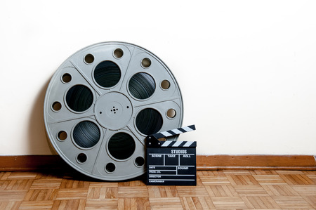 35 mm: 35 mm cinema movie roll with clapper on wooden floor and white wall background Stock Photo