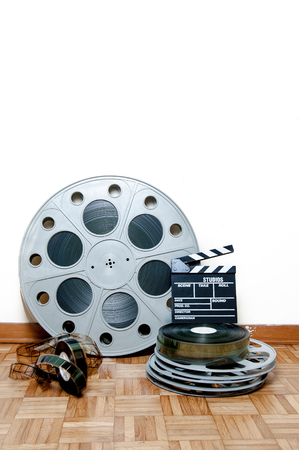 35 mm: 35 mm cinema movie roll and reels with clapper and filmstrip on wooden floor and white wall background