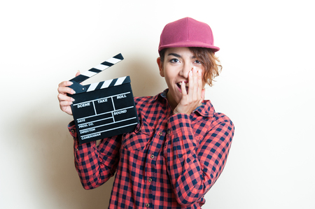 audition: Girl in red shirt and cap smiling and showing movie clapper on white background
