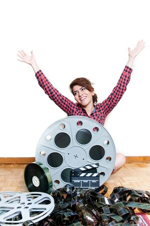 woman arms up: Young smiling woman arms up sits on wooden floor behind big original cinema movie reel Stock Photo