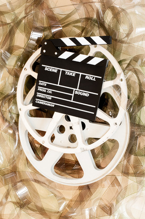 35: Cinema movie reel and clapper board with 35 mm unrolled filmstrip background, vertical frame Stock Photo