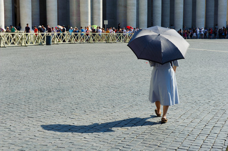 papal audience: ROME, ITALY, VATICAN CITY JULY 4th 2015 Woman with umbrella walking to the queues of tourists in St Peter square