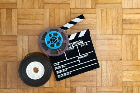 super 8: Movie clapper board with super 8 and 35 mm coloured film reels on wooden floor