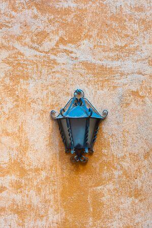 garden lamp: Outdoor garden lamp on rough coarse orange wall, vertical frame Stock Photo