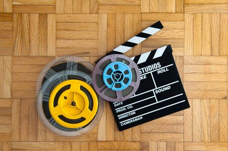 super 8: Movie clapper board cinema and super 8 coloured film reels horizontal frame on wooden floor Stock Photo