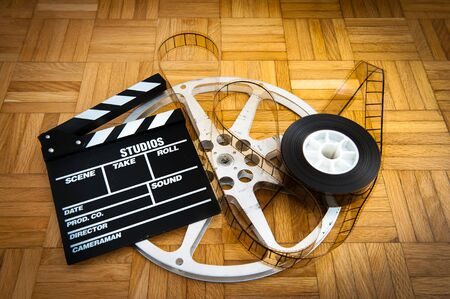 35: Cinema movie clapper board with 35 mm filmstrip and reel on wooden floor