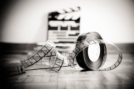 35 mm: 35 mm cinema film reel and out of focus movie clapper board in background on wooden floor in vintage black and white Stock Photo