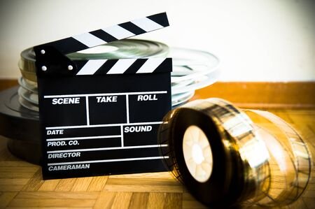 35 mm: Cinema movie clapper board and 35 mm film reel on wooden floor selective focus Stock Photo
