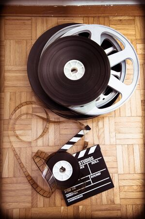35 mm: Cinema movie clapper board and 35 mm film reel on wooden floor vintage color effect vertical frame