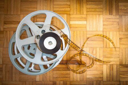 cinema film: 35 mm movie filmstrip and cinema reel on wooden floor Stock Photo