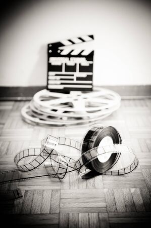 35 mm: 35 mm cinema film reel and out of focus movie clapper board in background on wooden floor in vintage black and white vertical frame