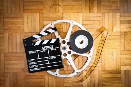 35 mm: Cinema movie clapper board with 35 mm filmstrip and reel on wooden floor