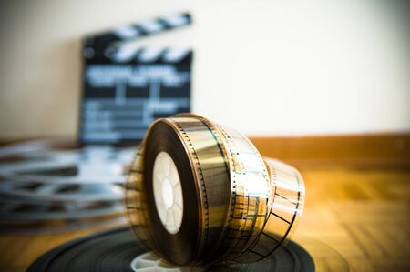 35 mm: 35 mm cinema film reel and out of focus movie clapper board in background on wooden floor Stock Photo