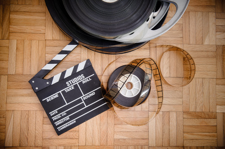 35 mm: Cinema movie clapper board and 35 mm film reel on wooden floor vintage color effect Stock Photo