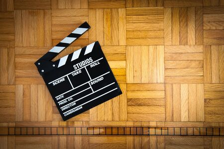 35 mm: Cinema movie clapper board and 35 mm horizontal line filmstrip on wooden floor Stock Photo
