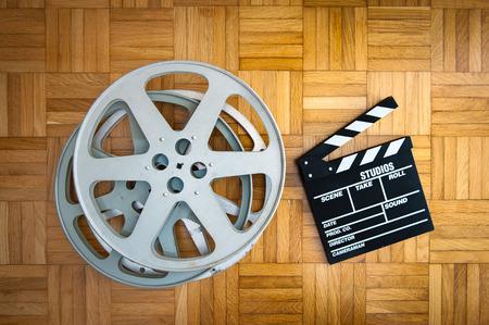 board of director: Cinema movie clapper board with film reel on wooden floor