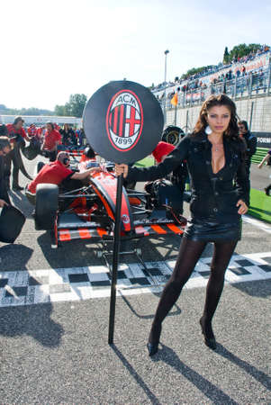 formula car: VALLELUNGA CIRCUIT, ROME, ITALY - NOVEMBER 2 2008. Grid girl and superleague formula car on circuit starting line
