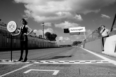 starting line: VALLELUNGA CIRCUIT, ROME, ITALY - NOVEMBER 2 2008. Grid girl on starting line dramatic black and white