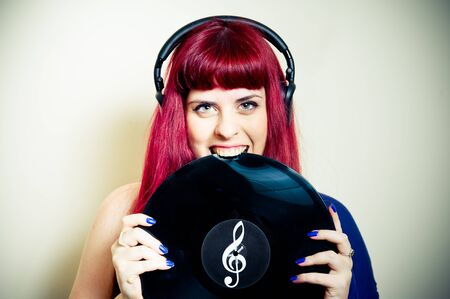 sound bite: Young pretty redhead woman smiling and biting vinyl record close up Stock Photo