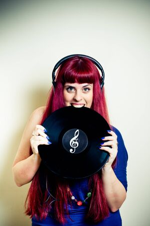 sound bite: Young pretty redhead woman with headphones biting vinyl record with treble clef symbol