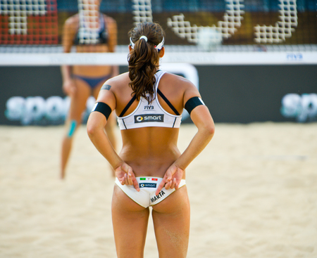 world championships: ROME, ITALY - JUNE 15 2011. Beach volleyball world championships. Italian player Marta Menegatti giving sign to her teammate, view from back