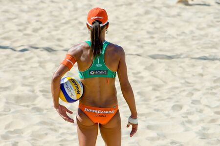 silva: ROME, ITALY - JUNE 18 2011. Beach volleyball world championships. Brazilian woman player Juliana Silva with ball during a match view from the back